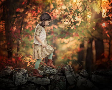Lilia Alvarado LITTLE GIRL CLIMBING ROCKS IN AUTUMN FOREST Children
