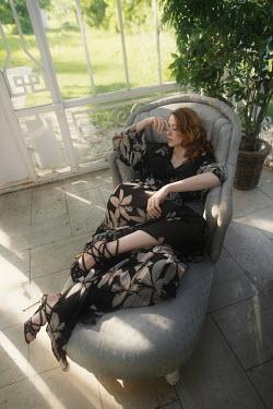 Tatiana Mertsalova YOUNG WOMAN SITTING IN GARDEN CONSERVATORY Women