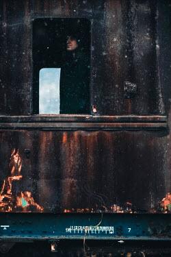 Dragan Todorovic MAN LOOKING OUT DERELICT TRAIN WINDOW Men