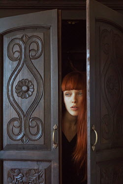 Marta Bevacqua YOUNG RED HAIRED WOMAN HIDING BY DOORS Women
