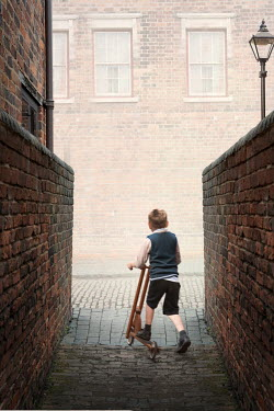 Lee Avison 1940s boy in an alleyway on a scooter Children