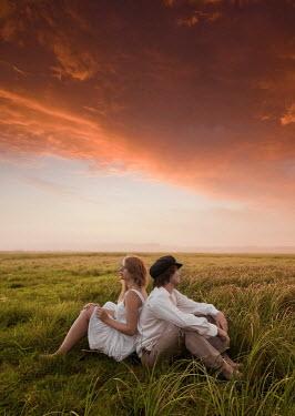 Leszek Paradowski COUPLE SITTING IN FIELD AT SUNSET Couples