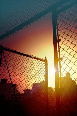 Miguel Sobreira city Buildings Through Fence at Sunset Gates