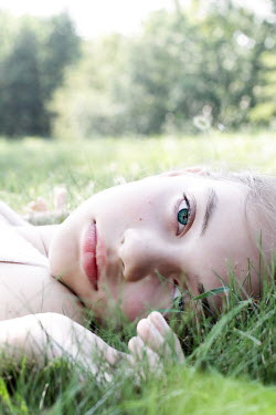 Stephanie Frey YOUNG GIRL WITH GREEN EYES LYING ON GRASS Children