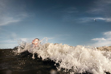 Mary Schannen BOY SWIMMING IN SEA WITH BIG WAVE Children