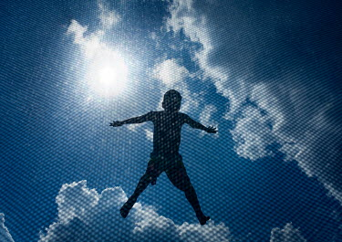Mary Schannen BOY TRAMPOLINING WITH SUN AND BLUE SKY Children