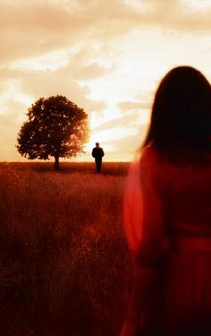 Ilona Wellmann COUPLE STANDING APART IN FIELD AT SUNSET Couples