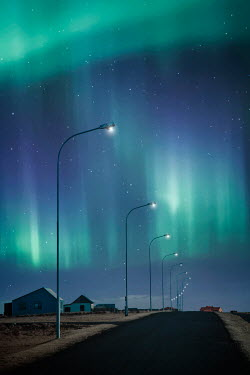 Evelina Kremsdorf road and streetlights under northern lights Villages