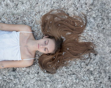 Inna Mosina YOUNG BRUNETTE WOMAN LYING ON FEATHERS Women