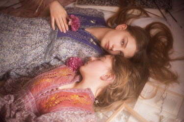 Vivienne Mok TWO HIPPY TEENAGE GIRLS LYING ON FLOOR Children