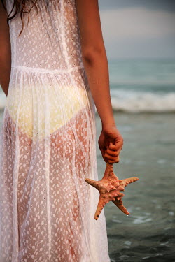 Maria Petkova YOUNG WOMAN HOLDING STARFISH BY THE SEA Women