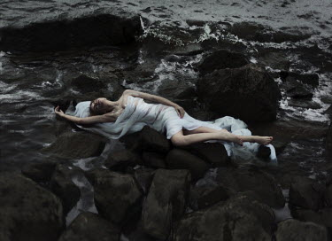 Kirill Sakryukin YOUNG WOMAN LYING ON ROCKS BY SEA Women