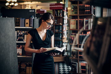 Maxim Guselnikov YOUNG WOMAN WEARING GLASSES IN BOOK SHOP Women