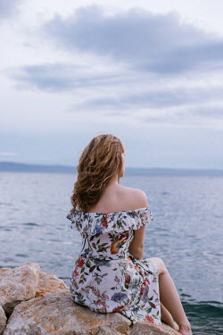 Nina Masic WOMAN IN FLORAL DRESS SITTING BY SEA Women