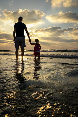 Stephen Carroll FATHER AND DAUGHTER IN SEA AT SUNSET Men