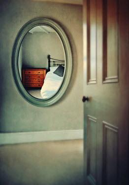 Lyn Randle OPEN BEDROOM DOOR WITH MIRROR REFLECTING BED Interiors/Rooms