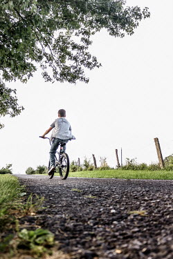 Stephen Carroll TEEN BOY RIDING BIKE ON COUNTRY ROAD Children