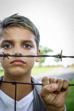 Stephen Carroll TEEN BOY BEHIND RUSTY BARBED WIRE Children