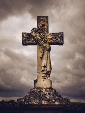 Jane Morley WEATHERED CROSS TOMBSTONE UNDER CLOUDY SKY Statuary/Gravestones