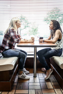 Stephen Carroll TWO TEENAGERS DRINKING COFFEE IN DINER Women