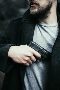 Laura Ranftler MODERN MAN WITH BEARD HOLDING GUN Men