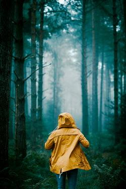 Rekha Garton WOMAN WEARING YELLOW COAT IN FOREST Women