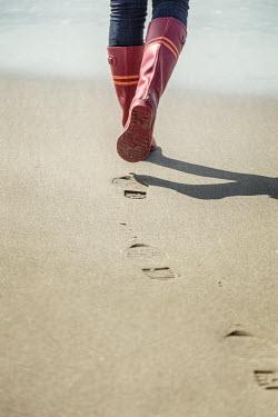 Evelina Kremsdorf WOMAN IN WELLINGTONS WALKING ON BEACH Women