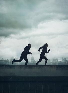 Mark Owen COUPLE RUNNING IN FOGGY CITYSCAPE Couples