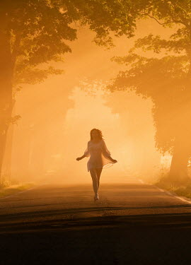 Leszek Paradowski WOMAN WALKING ON COUNTRY ROAD IN GOLDEN SUNLIGHT Women