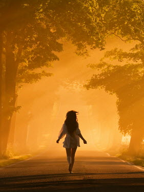 Leszek Paradowski WOMAN RUNNING BAREFOOT ON COUNTRY ROAD IN GOLDEN SUNLIGHT Women