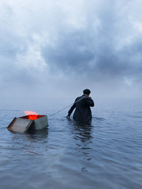 Leszek Paradowski MAN PULLING BOX OF FIRE IN SEA Men