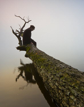 Leszek Paradowski MAN SITTING ON FALLEN TREE ON LAKE Men