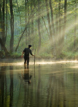 Leszek Paradowski MAN WITH STICK IN SUNLIT RIVER Men