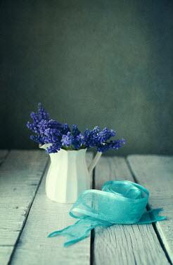 Svetlana Bekyarova BLUE FLOWERS IN JUG AND RIBBON ON TABLE Flowers