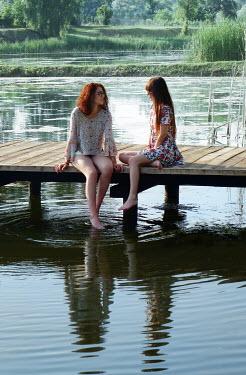 Ilona Wellmann TOW GIRLS SITTING ON JETTY BY LAKE IN SUMMER Women