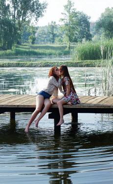 Ilona Wellmann GIRL WHISPERING TO FRIEND SITTING ON JETTY BY LAKE Women