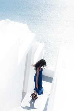 Ollie Taylor WOMAN WALKING BY WHITEWASHED BUILDINGS BY SEA Women