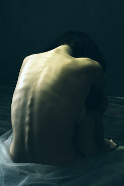 Alina Zhidovinova NUDE WOMAN FROM BEHIND SITTING IN DARK ROOM Women