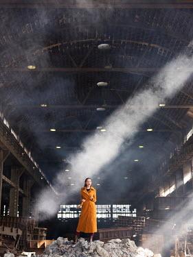 Aida Redzepagic WOMAN STANDING ON RUBBLE IN DERELICT WAREHOUSE Women