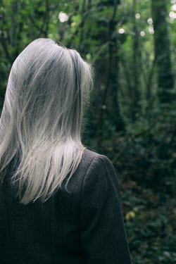 Clayton Bastiani WOMAN WITH GREY HAIR STANDING IN FOREST Old People