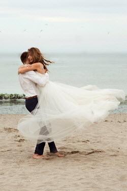 Maria Petkova JOYFUL BRIDE AND GROOM EMBRACING ON SANDY BEACH Couples