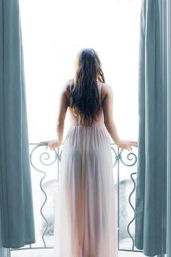 Ildiko Neer Young woman standing on balcony Women