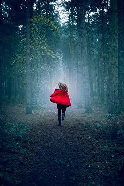 Laura Ranftler WOMAN IN RED COAT RUNNING IN FOREST Women