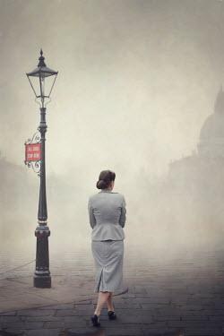 Lee Avison 1940s woman walking on a smoggy cobbled street Women