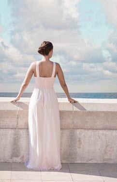 Ildiko Neer Woman in pink dress on balcony Women