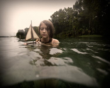 Erika Masterson GIRL WITH TOY BOAT IN LAKE Children