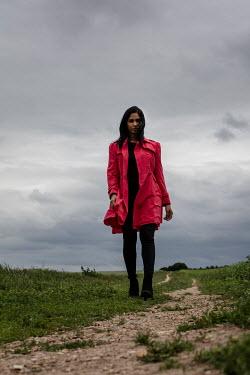 Stephen Mulcahey WOMAN IN RED COAT WALKING IN COUNTRYSIDE Women