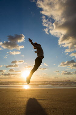 Mohamad Itani BOY LEAPING ON BEACH AT SUNSET Children