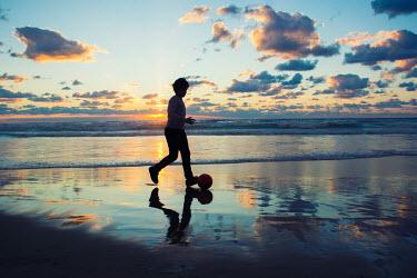 Mohamad Itani BOY PLAYING FOOTBALL ON BEACH AT SUNSET Children