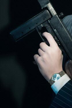 Ysbrand Cosijn CLOSE UP OF RETRO MAN HOLDING MACHINE GUN Men